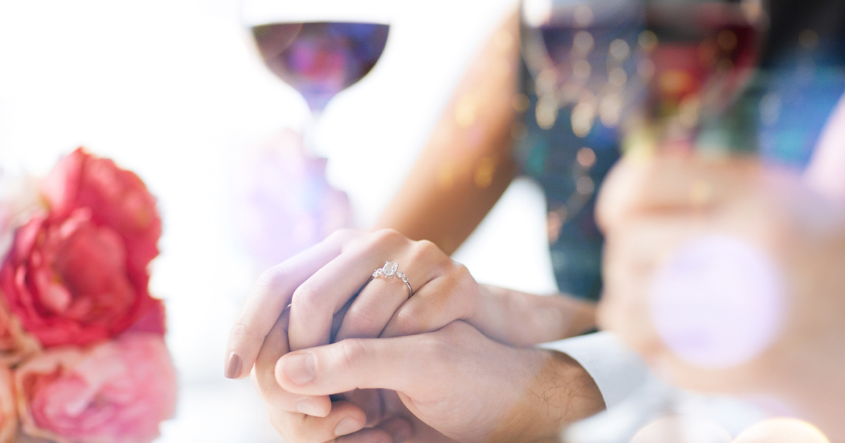 Woman wearing an engagement ring and holding hands with her fiance