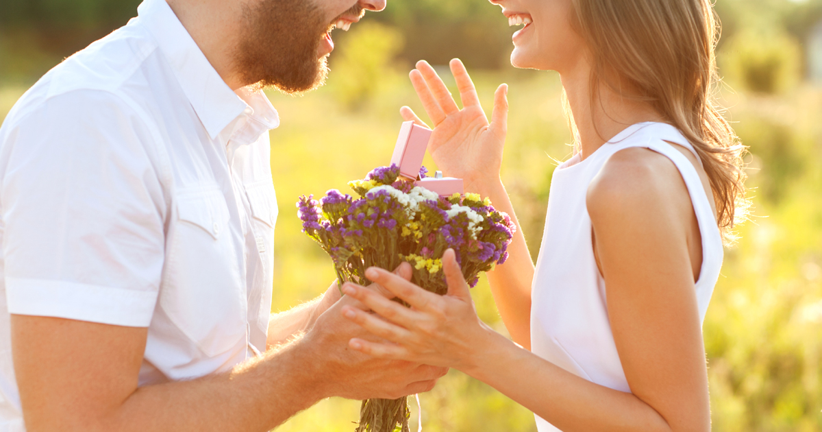 man with bunch of flowers and engagement ring proposing to a woman