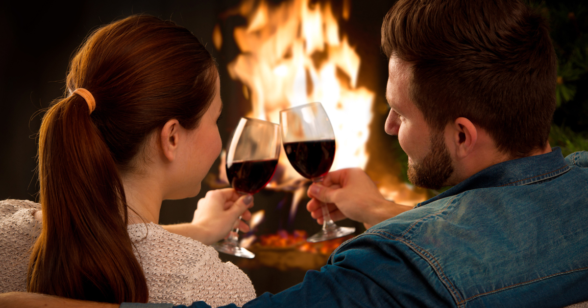 A couple drinking wine in front of a fire