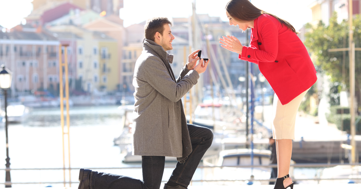 Man down on one knee proposing to a woman