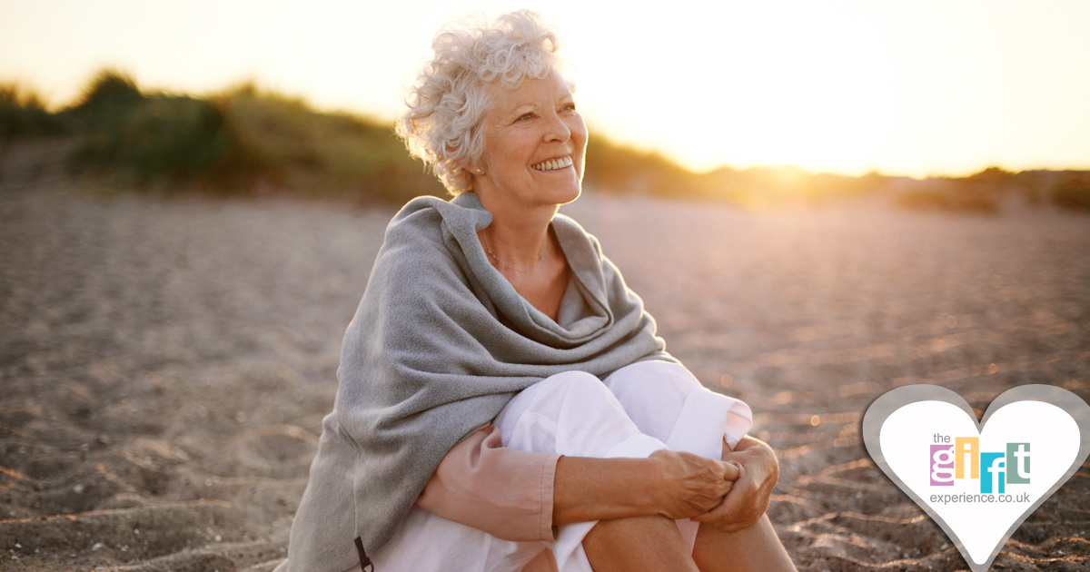 70 year old woman sitting on a beach in the sun