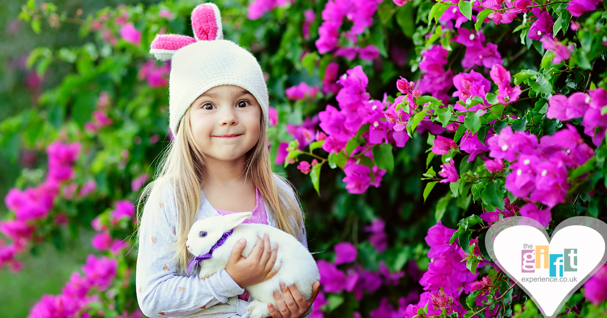 little girl wearing rabbit ears and holding an easter bunny