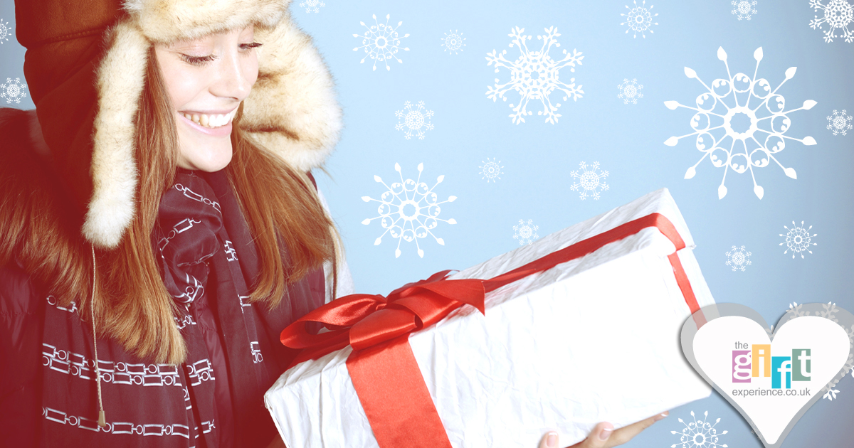 Girl in a winter hat holding a christmas gift