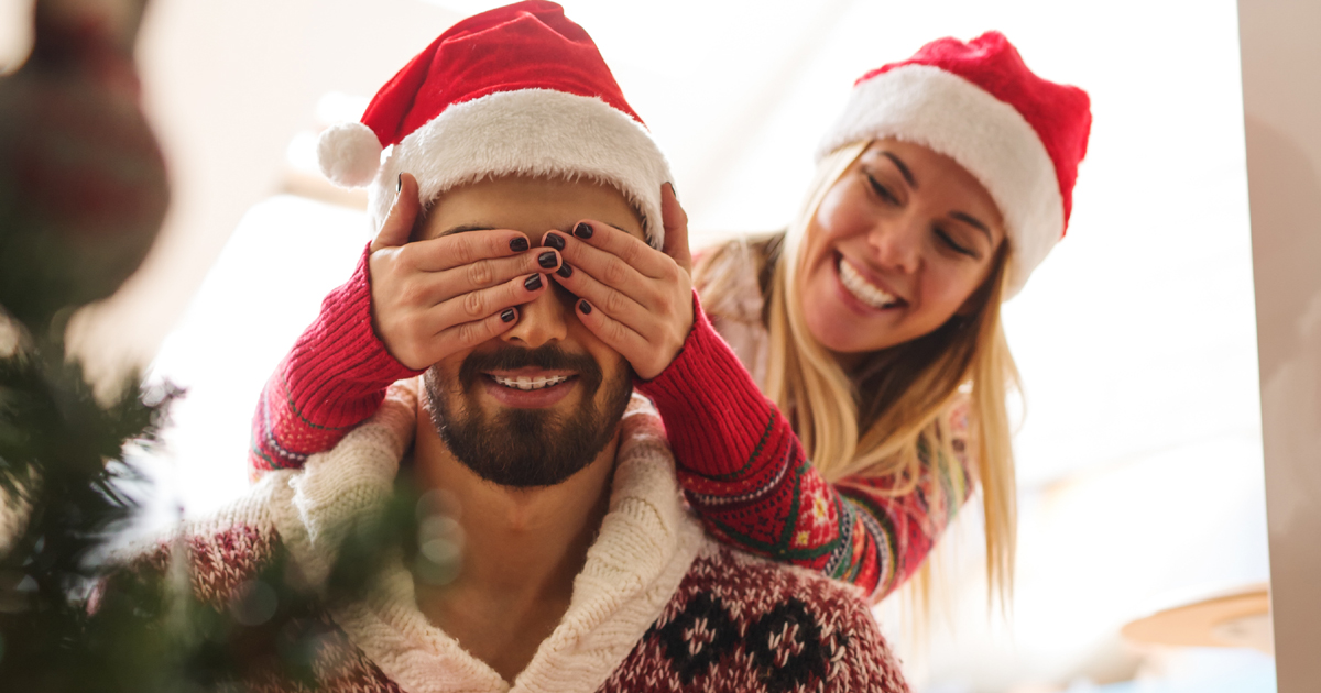 A woman covering her partner's eyes by a Christmas tree