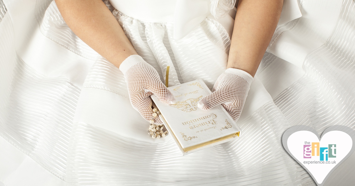 A girl holding a bible and rosery for her Holy Communion