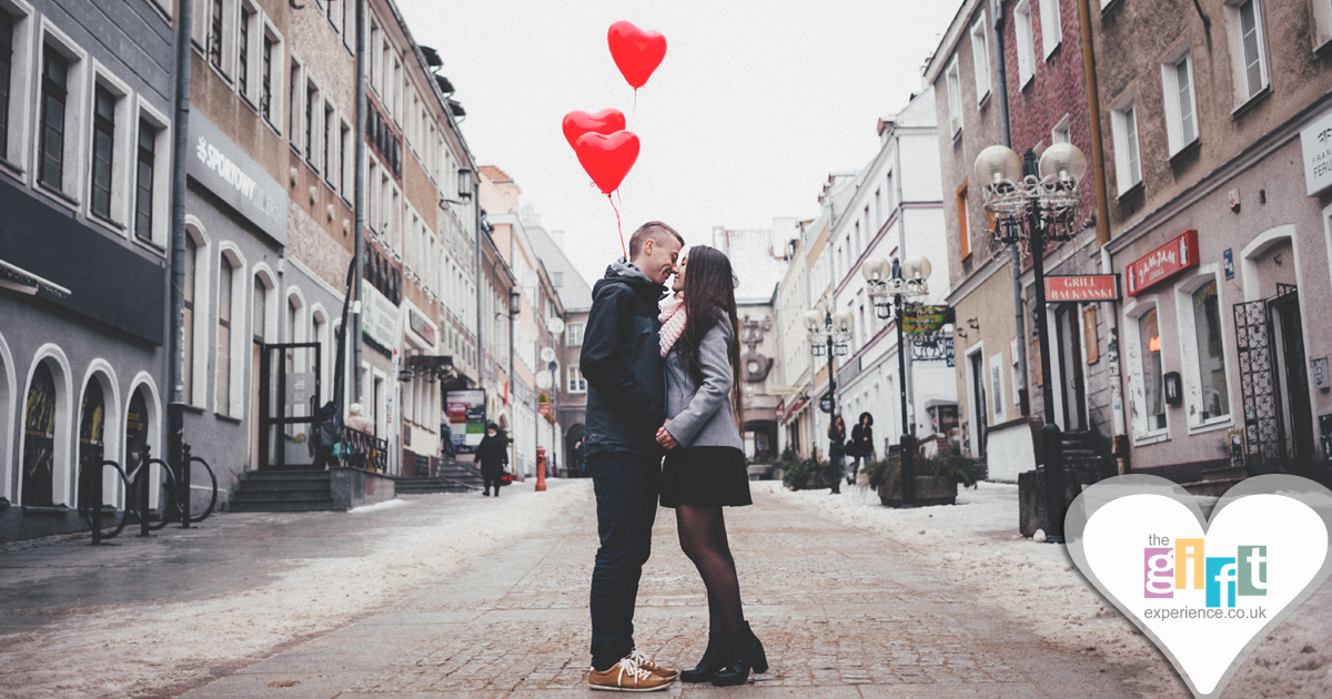 couple standing together holiding heart shaped balloons