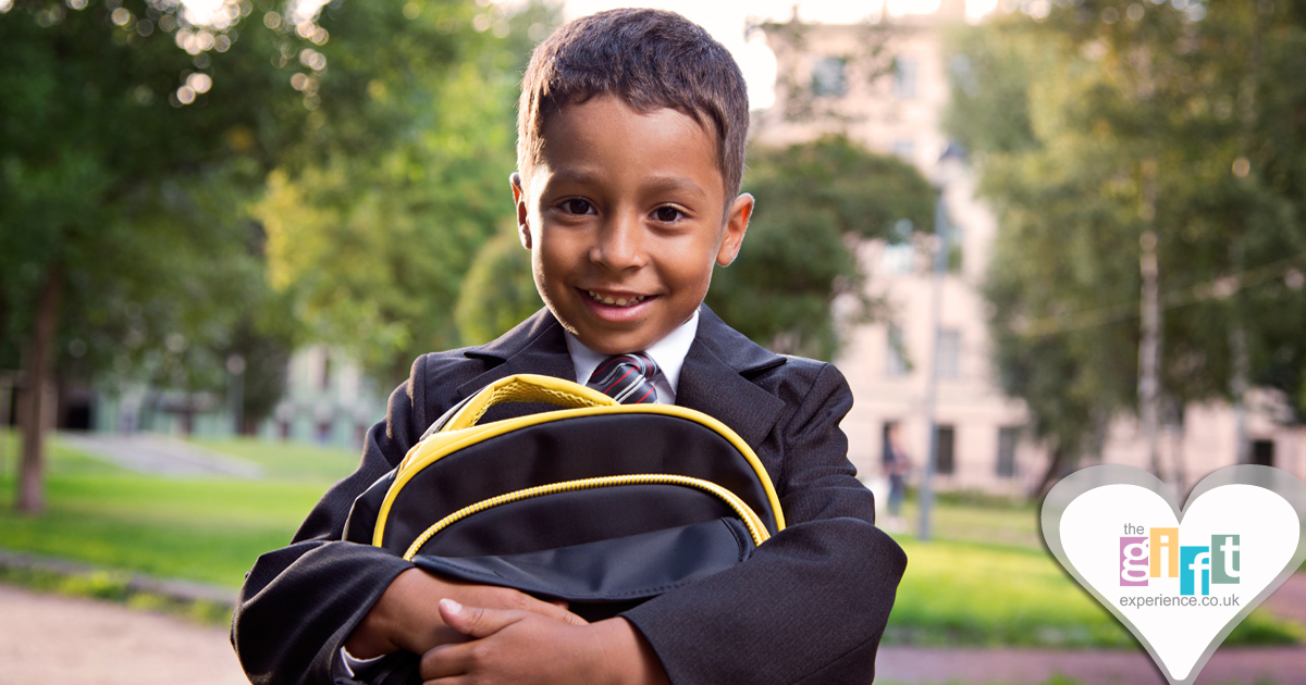 a little boy in a school uniform with a backpack all ready for school