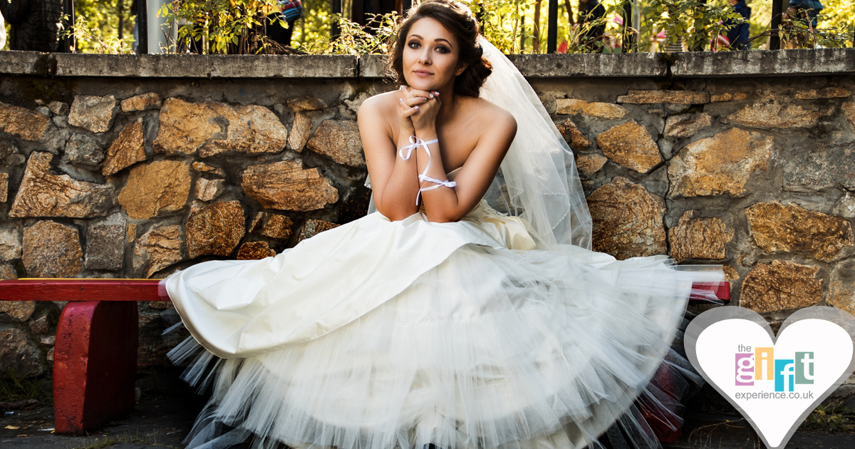 A woman sat on a bench in a wedding dress